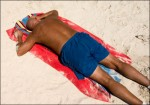 A man sun tanning on the beach