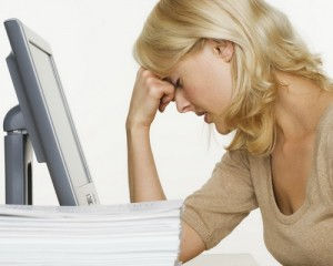 Frustrated Woman at Computer With Stack of Paper [Image Credit: Corbis]