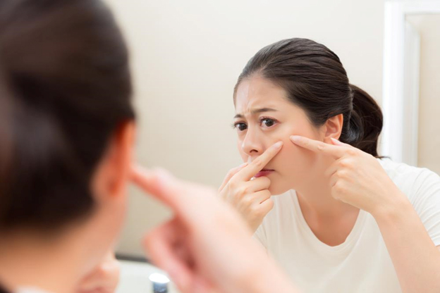 woman checking for acne on face